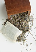 Dried lavender flowers being filled into a teabag