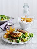 Spicy chicken burger with chips and a cucumber salad