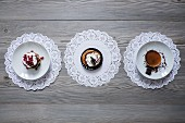 Three different dessert tartlets on paper doilies (seen from above)