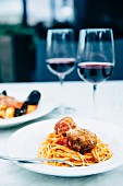 Pasta with meatballs, a seafood platter and two glasses of wine on the table