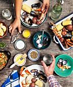 Hände beim Verzehr von Meeresfrüchten an gedecktem Tisch (Aufsicht)