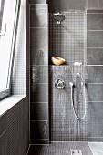 Grau gefliester Duschbereich mit Mosaikfliesen und Wandarmaturen