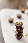 A stack of chocolate bites with pistachio nuts