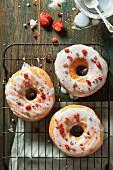 Drei glasierte Donuts mit gefriergetrockneten Erdbeerstücken und Silberperlen auf Abkühlgitter