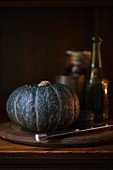 A green pumpkin on a wooden plate