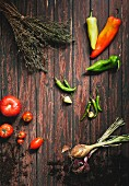 Pointed peppers, chilli peppers, tomatoes, onions and savoury on a wooden surface