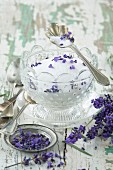 Lavender sugar in a glass bowl with fresh lavender flowers in the foreground