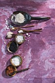 Various types of salt on spoons and in dishes on a purple surface (seen from above)
