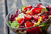 A mixed vegetable salad with pomegranate seeds in a glass bowl