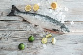 Fresh salmon with ice cubes and citrus fruits on a wooden surface