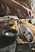 Raw salmon on a piece of baking paper being sprinkled with salt