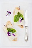 Olive baguette topped with alpine cheese, bloodwort and tufted pansies