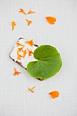 Slice of bread topped with cream cheese, and wasabi leaf and marigold petals
