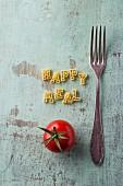 Schriftzug Happy Meal aus Buchstabennudeln daneben Gabel und Tomate