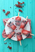 Homemade summer berry ice lollies on a plate (seen from above)