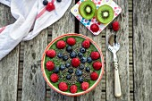 A green smoothie bowl with kiwis, blueberries, raspberries and chia seeds