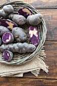 Purple potatoes, whole and halved, in a wicker basket
