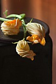 Three courgette flowers on a rustic surface