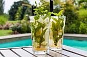Zwei Gläser Mojito auf Terrassentisch am Pool