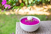 A dragon fruit smoothie bowl on a table outside