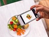 Frau fotographiert Gericht mit Quinoa und Salat auf Tisch mit Smartphone
