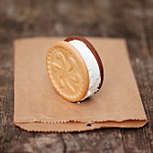 An ice cream sandwich standing upright on a paper bag