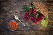 A jar of rowan berry jam next to a wicker basket of rowan berries (seen from above)