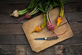 Red, white and yellow organic turnips on a wooden chopping board (seen from above)