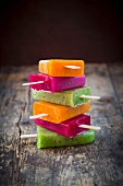 A stack of various ice lollies on a wooden surface