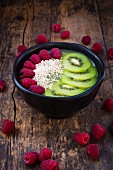 A smoothie bowl with amaranth, chia seeds, raspberries and kiwi