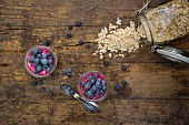 Two glasses of overnight oats with blueberries and berry juice on a wooden surface