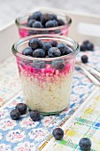 Glasses of overnight oats with blueberries and berry juice on a tray