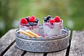 Two glasses of chia pudding with blueberries and raspberries on a metal tray