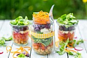 Rainbow salads in glasses with chickpeas, lamb's lettuce and red cabbage