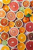 A whole mandarin surrounded by halved citrus fruits (seen from above)
