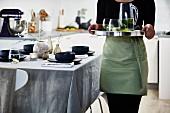 Frau serviert Tablett mit Getränken in der Küche