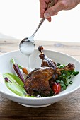 Side of vegetables with roasted duck leg being drizzled with sauce