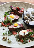 Grilled steak with fried quails eggs and salsa verde