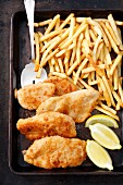 Chicken escalope, chips and lemon wedges on a baking tray