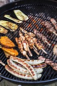Grilled kebabs, sausages and vegetables on a barbecue