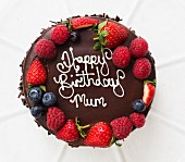 A birthday cake with chocolate glaze and fresh berries