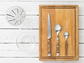 Kitchen utensils: a measuring jug, a glass bowl, a knife and spoons