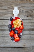 Waffle bites with fresh berries on a large enamel spoon