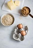 Backzutaten: Butter, Haferflocken, Eier und brauner Rohrzucker