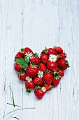 A heart made from fresh strawberries on a white wooden surface