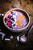 A smoothie bowl with oats, chia seeds, grated coconut, almond butter and blueberry compote