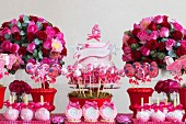 Various cake pops, sweets and birthday cakes between bunches of roses