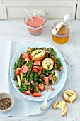Spinach salad with strawberries, green asparagus, goat's cheese croutons and strawberry sauce