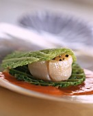 A scallop in a savoy cabbage leaf on a pool of sauce