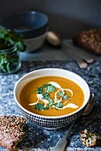 Sweet potato soup with yoghurt and coriander and a fresh seeded bread next to it